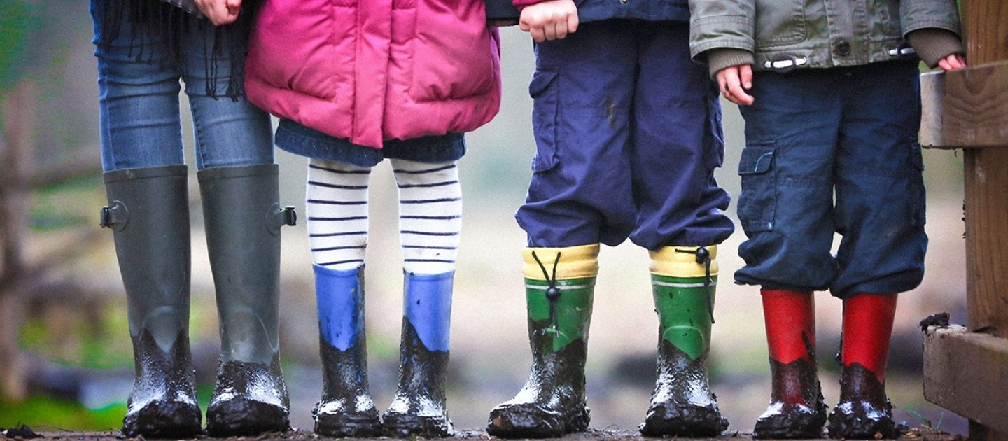 Four children standing up in wellington boots